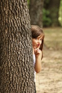 A cute little girl is hiding behind a tree and peeks around holding her finger to her lips saying, shhh